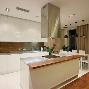 Kuchnia połączona z jadalnią tworzy piękne, spójne wnętrze. Chłód bieli ocieplają drewniane elementy. Fot. Svoya studio.