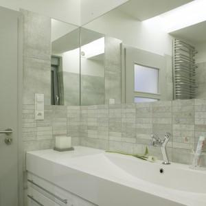 Dekoracyjną rolę w szarej, minimalistycznej łazience pełni kompozycja okładzin stworzona z płytek gresowych w dużym formacie i przyciętych listew dekoracyjnych. Przyklejona do ściany tafla lustra przechodzi także na sąsiednią ścianę dając ciekawy efekt głębi. Projekt: Piotr Wełniak. Fot.  Monika Filipiuk-Obałek.