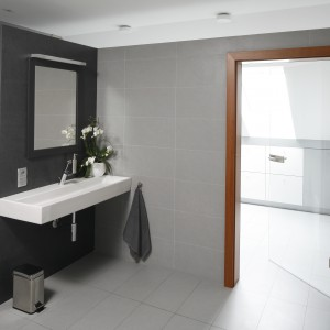 Wyposażenie zostało ograniczone do minimum, jednak łazienka jest funkcjonalna i wygodna,  a szare kolory ścian i płytek zapewniają elegancki charakter. Projekt: Piotr Stanisz. Fot. Bartosz Jarosz.