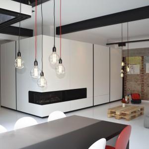 Wnętrze mieszkania nawiązuje do poprzedniego przeznaczenia budynku. Z industrialnym charakterem fabryki koresponduje cegła na ścianie w salonie, paleta pełniąca funkcję stolika kawowego oraz dekoracyjne żarówki z widocznym okablowaniem, pełniące rolę lamp. Fot. Aeon Architecten.