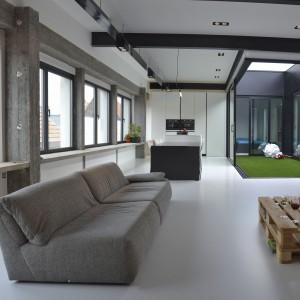 Przestrzeń dzienną zlokalizowano na przestronnym, otwartym planie. W całym pomieszczeniu zastosowano jednorodną, białą podłogę, która dodatkowo wizualnie powiększa, już i tak dużą, przestrzeń. Fot. Aeon Architecten.