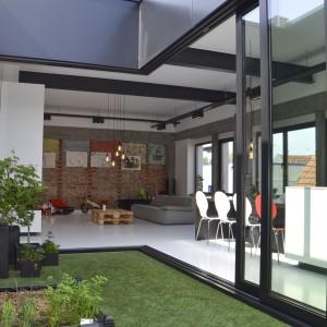 Panoramiczne bezprogowe przeszklenia pozwalają całkowicie otworzyć przestrzeń mieszkania na zewnątrz, zyskują płynne przejście pomiędzy wnętrzem, a otoczeniem mieszkania. Fot.  Aeon Architecten.