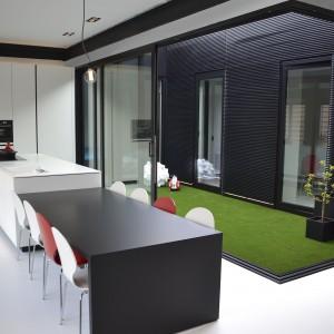 Soczysta zielona trawa porastająca dziedziniec pełni rolę elementu dekoracyjnego mieszkania. Wraz z czerwonymi krzesłami ożywia monochromatyczne czarno-białe wnętrze. Fot.  Aeon Architecten.