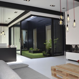Widoczny z wnętrza domu dziedziniec stanowi integralny element dekoracyjny wnętrza. Dzięki kształtowi bryły budynku oraz sposobowi, w jaki rozmieszczono wielkowymiarowe przeszklenia, przyjmuje on formę kubika w rogu pomieszczenia. Fot. Aeon Architecten.