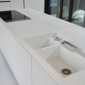Kuchnia to królestwo minimalistycznych form. Biały zlewozmywak wpuszczony w blat kuchenny, chowa się w otaczającej go bieli. Baterię kuchenną można złożyć do pozycji leżącej, tak aby nie wystawała poza linię blatu. Jedną płaszczyznę w blatem stanowi również kuchenka indukcyjna. Fot. Aeon Architecten.