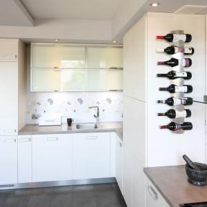 Gładkie fronty wysokiej zabudowy kuchennej nadają kuchni lekkiego i nowoczesnego charakteru. Połyskujące fronty szafek stwarzają wrażenie większego wnętrza. Projekt: Arek Grzędzicki. Fot. Bartosz Jarosz.