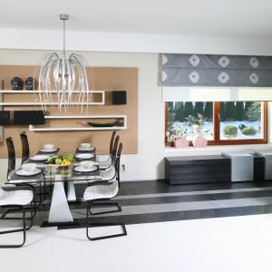 Kompozycja kontrastujących bieli i czerni koresponduje z półkami na ścianie jadalni. Białe elementy tworzą spójną całość z meblami kuchennymi i krzesłami w kuchni.  Projekt: Małgorzata Borzyszkowska. Fot. Bartosz Jarosz.