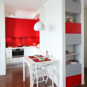 Niewielki stolik w białym kolorze udekorowany czerwonymi podkładkami komponuje się z kolorystyką mebli kuchennych. Projekt: Iza Szewc. Fot. Bartosz Jarosz.