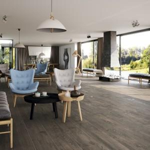 Płytki podłogowe marki Porcelanite imitujące tradycyjną podłogę drewnianą w ciemnym kolorze drewna. Fot. Porcelanite.
