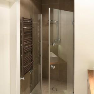 Wnęka w tym pomieszczeniu była idealna na prysznic.  Wystarczyło zamknąć ją drzwiami. Zastosowano rozwiązanie z dodatkową wąską ścianka, tak aby przy otwieraniu nie uderzyć o grzejnik na ścianie. Projekt: Agnieszka Ludwinowska. Fot. Bartosz Jarosz.