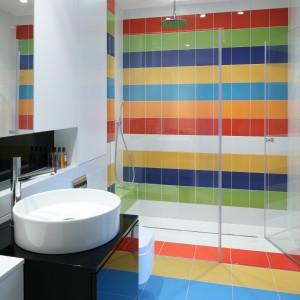 Prysznic umieszczony został w głębi pomieszczenia, a szerokość wnęki prysznicowej wyznaczają ściany łazienki. Tafla szkła - ścianka i drzwi - pozwoliła również na wyeksponowanie efektownej, kolorowej okładziny ceramicznej. Projekt: Katarzyna Kiełek,  Agnieszka Komorowska-Różycka. Fot. Bartosz Jarosz.