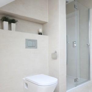 Wnęka w łazience na poddaszu została umieszczona pod skosem, a jej szerokość wyznacza ścianka działowa. W ten sposób prysznic oddzielony jest od strefy sanitarnej. Projekt:  Karolina i Artur Urban. Fot. Bartosz Jarosz.