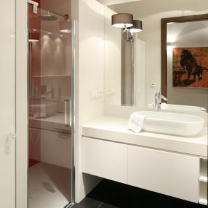 Tylko dwie ścianki działowe wystarczyły do tego, aby podzielić łazienkę na strefy i stworzyć wnękę prysznicową. Chociaż wnętrze jest niewielkie udało się stworzyć spory prysznic z dopasowanym wymiarowo brodzikiem. Został on zabudowany w płaszczyźnie podłogi, dlatego jej poziom jest taki sam w całym pomieszczeniu. Wnękę wyróżnia kontrastowy, czerwony kolor ściany, a zamknięta jest szklanymi drzwiami otwieranymi wahadłowo. Projekt: Małgorzata Galewska. Fot. Bartosz Jarosz.