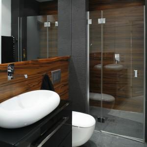 Wnęka jest nie tylko praktyczna, ale i efektowna.  Ściana za prysznicem jest wykończona odpowiednio zabezpieczonym fornirem. Z kolei odprowadzenie wody zapewnia odpływ punktowy, dlatego podłoga w całej łazience jest wykończona gresem. Drzwi prysznicowe są mocowane na zawiasach do wąskiej stałej ścianki szklanej. Dzięki temu drzwi bezproblemowe otwierają się pomimo, że blisko wnęki umieszczony jest sedes. Projekt: Monika i Adam Bronikowscy. Fot. Bartosz Jarosz.