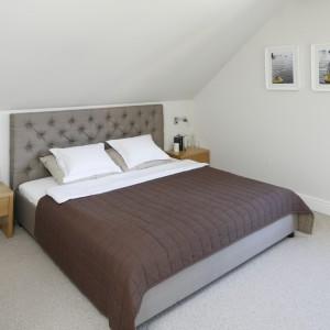Ulokowaną na poddaszu sypialnię ocieplają jasne beże. W jego odcieniu jest nie tylko ozdobne tapicerowane łoże, ale też wykładzina podłogowa. Fot. Bartosz Jarosz.