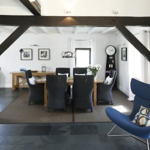 Przestronne jasne wnętrze urozmaicono różnymi błękitów. Rattanowe krzesła w jadalni, nowoczesny fotel, łupek kamienny na podłodze w barwie z pogranicza szarości i granatu nadają wnętrzu luksusowego charakteru. Fot. Bartosz Jarosz.
