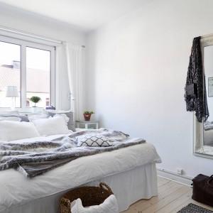 Przytulny klimat sypialnia zawdzięcza zastosowanym tkaninom. Miękka, puchata narzuta z motywem zwierzęcym ociepla białe, zimne wnętrze. Ozdobna rama, w którą oprawiono lustro nadaje pomieszczeniu wytwornego szyku. Fot. Stadshem.