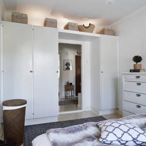 Wejście do sypialni od strony wnętrza pomieszczenia zabudowano pojemnymi szafkami. Nie poprowadzono ich jednak ku samemu sufitowi, zostawiając wolne miejsce, które może posłużyć za półkę, pełniącą praktyczną lub dekoracyjną funkcję. Fot. Stadshem.