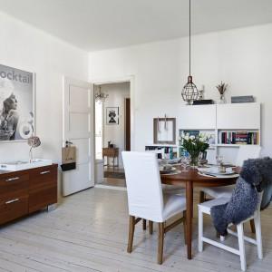 W jadalni panuje przytulny, domowy klimat. Pomieszczenie zawdzięcza go drewnianej podłodze i meblom w ciepłych odcieniach drewna. Fot. Stadshem.