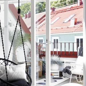 Z salonu można przejść bezpośrednio na taras. Prowadzą do niego przesuwne drzwi balkonowe o niskim progu. Wielkowymiarowe przeszklenia i nowoczesna forma stolarki stwarzają wrażenie przenikania się przestrzeni patio z salonem. Fot. Stadshem.