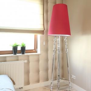 Stojąca lampa z czerwonym abażurem oraz stylizowaną podstawą stanowi wyraźny, kolorystyczny akcent w sypialni. Projekt: Karolina Łuczyńska. Fot. Bartosz Jarosz.