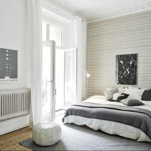 Tapeta w poziome pasy optycznie poszerza wysoką i wąską sypialnię. Fot. Stadshem.