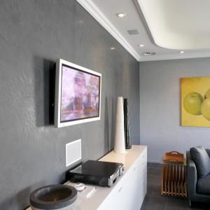 Ciemny odcień szarości na ścianie salonu z telewizorem skontrastowano z jasnym odcieniem pozostałych jego ścian. dodatkowe efekty zdobnicze daje ciekawa struktura pierwszej z farb. Fot. Dekoral.