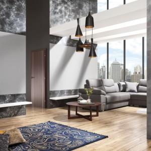 W salonie stonowane szarości ścian przełamuje  ciepło drewnianej podłogi, podkreślając loftowy charakter całej aranżacji. Fot. Magnat.