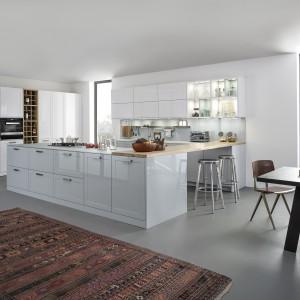 Świeża, przytulna aranżacja kuchni. Nowoczesne białe meble na wysoki połysk zestawiono z przytulnym dywanem i ciężkim drewnianym stołem. Fronty dolnych szafek mają uchwyty, podczas gdy górna zabudowa została wykonana w maksymalnie minimalnym stylu. Drewniany blat pełniący funkcję łącznika pomiędzy wyspą a zabudową kuchenną oraz schowek na wino nadają kuchni skandynawskiego charakteru. Fot. Leicht, kolekcja Carre 2 LG 2014.
