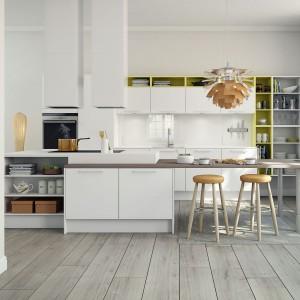 W tej kuchni postawiono na współczesne i funkcjonalne rozwiązania. Blat kuchenny przechodzi płynnie w stół z jednej strony, z drugiej przykrywa funkcjonalne półki. Biel tworzy stonowaną kompozycję z drewnem, ożywioną żółtymi akcentami na ściennych półkach. Fot. HTH.