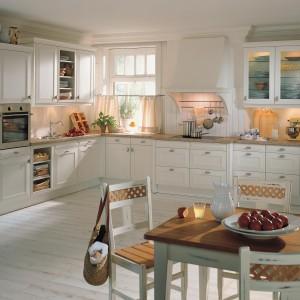 Piękne klasyczne meble do rustykalnych i angielskich kuchni. Biały kolor ocieplono drewnem i kamiennym blatem w miodowym kolorze. Ozdobne fronty, klasyczne uchwyty i przeszklone drzwiczki podwieszanych szafek tworzą domową, tradycyjną atmosferę. Fot. Rational, kolekcja Tio.