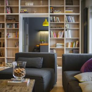 Na ścianie pomiędzy salonem i kuchnią zlokalizowano wysoką zabudowę, sięgającą sufitu. Rozciąga się ona na powierzchnię całej ściany i posłużyła za obszerną biblioteczkę. Fot. Michał Mazurowicz.