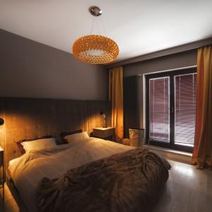 W sypialni królują ciepłe barwy. Jesienna paleta kolorów prezentowana przez czekoladowe brązy i złote żółcie nadaje wnętrzu przytulnego charakteru. Na uwagę zasługuje duży tekstylny zagłówek, poprowadzony na szerokości całej ściany za łóżkiem. Jego miękka faktura i ciepła barwa dodatkowo ocieplają wnętrze. Fot. Michał Mazurowicz.