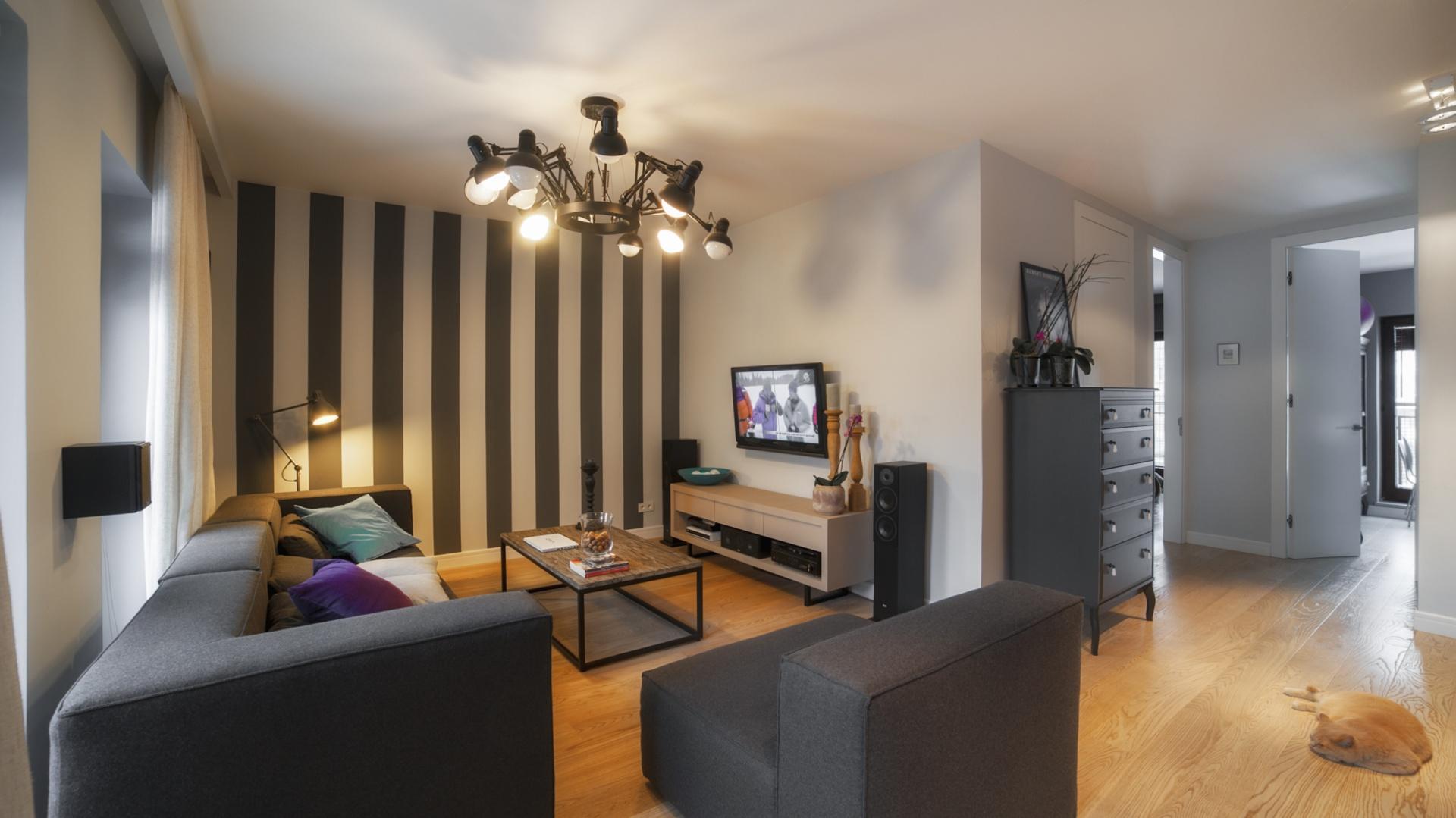 Kącik wypoczynkowy w salonie zlokalizowano we wnęce. Najgłębiej położoną ścianę pokrywa tapeta w pionowe pasy w tym samym kolorze co meble wypoczynkowe. Delikatny, elegancki detal dekoracyjny powiększa optycznie wysokość wnętrza i jednocześnie skraca wnękę, unikając efektu