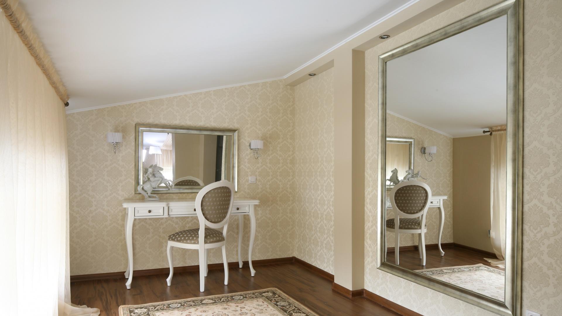 Eleganckie krzesło, stylizowana forma toaletki,  ozdobne kinkiety oraz lustra umieszczone w połyskujących ramach - strefa toaletki została doskonale przemyślana. Projekt: Małgorzata Goś. Fot. Bartosz Jarosz.