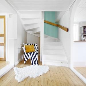 Między kuchnią, a salonem znajduje się mały korytarz. Z jego przestrzeni na górę domu prowadzą białe, kręte schody. We wnęce pod schodami postawiono krzesło, wyłożone wzorzystą, czarno-białą narzutą. Fot. Vastanhem.
