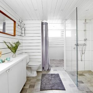 Obok łazienki zaplanowano przestronną pralnię. Prowadzi do niej wnęka drzwiowa, w której zamiast drzwi powieszono lekką kurtynę, komponującą się kolorystycznie z dywanem na podłodze łazienki. Fot. Vastanhem.
