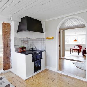 Kuchnię urządzono w stylu new country. Pękająca drewniana belka zachowana w naturalnym kolorze drewna oraz stary tradycyjny piec w rogu pomieszczenia nadają kuchni rustykalnego charakteru. Fot. Vastanhem.