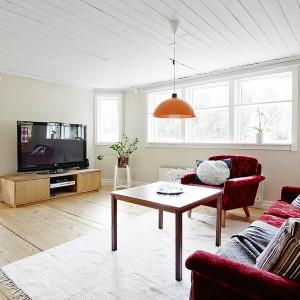 Niski sufit potęguje wrażenie domowego klimatu w salonie, stworzone przez przytulne meble. Powierzchnię sufitu pomalowano na biało, podczas gdy ściany wykończono jasnym beżem. To z kolei zabieg optyczny dodający pomieszczeniu kilku centymetrów wysokości - tak aby przytulność nie zamieniła się we wrażenie ścisku i ciasnoty. Fot. Vastanhem.