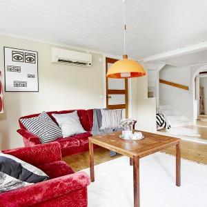W salonie przytulny nastrój buduje miękki, aksamitny komplet wypoczynkowy w czerwonym kolorze oraz liczne poduchy o różnych barwach i wzorach. Fot. Vastanhem.