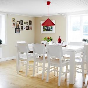 W sąsiadującej z kuchnią jadalni postawiono biały stół jadalniany. Pomieszczenie jest na tyle przestronne, że w razie potrzeby spokojnie można dostawić drugi o takim samym rozmiarze. Beżowe ściany, białe meble i drewniana podłoga tworzą subtelną, delikatną aranżację. Stonowane neutralne kolory ożywione zostały mocnymi czerwonymi akcentami w postaci wiszącej nad stołem lampy i dekoracyjnego szkła. Fot. Vastanhem.