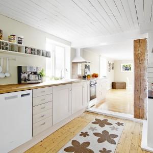 Długi blat kuchenny rozciąga się wzdłuż ściany na dwa sąsiadujące ze sobą pomieszczenia. Zaczyna się w kuchni, a kończy w jadalni. Efekt wizualny jest tym bardziej interesujący, gdyż prostopadle do aneksu kuchennego poprowadzony jest biały drewniany próg który wyraźnie oddziela od siebie oba pomieszczenia. Fot. Vastanhem.