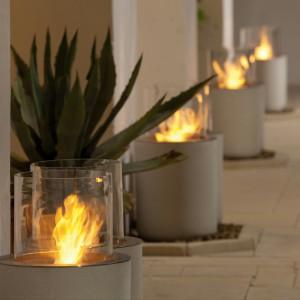 Szklany cylinder kominka Jar Commerce został osadzony na masywnej, betonowej podstawie. Kontrast ciężkiego betonu oraz lekkiego szkła to doskonały pomysł na dekoracyjne oświetlenie tarasu i ogrodu. Fot. Planika.
