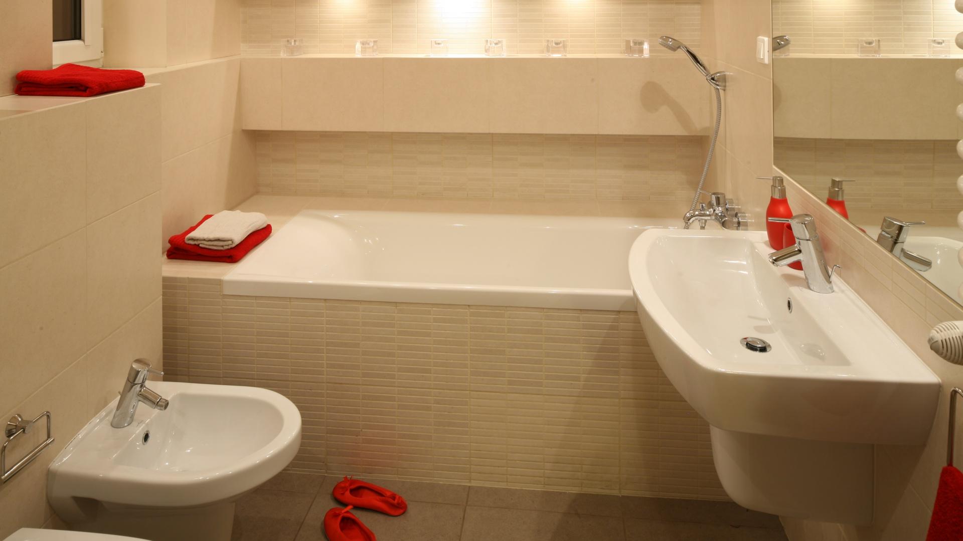 W skąpanej w beżach łazience panuje aura spokoju i relaksu, a czerwone dodatki sprawiają, że aranżacja ma wyrazisty charakter. Projekt: właściciele. Fot. Bartosz Jarosz.