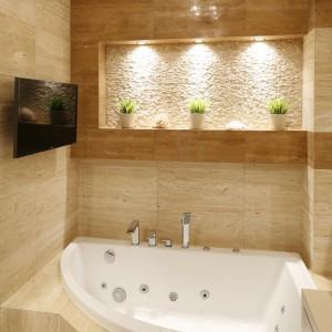 Odcienie beżu zdobią całą łazienkę, a podświetlana wnęka nad wanną wykończona kamienną mozaiką pełni rolę fantastycznej dekoracji. Projekt: Jolanta Kwilman. Fot. Bartosz Jarosz.