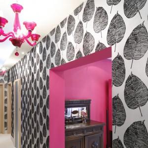 Na ścianie w korytarzu położono szarą tapetę z motywem liści. Kontrastuje ona i pięknie eksponuje różowe akcenty we wnętrzu. Fot. Bartosz Jarosz.