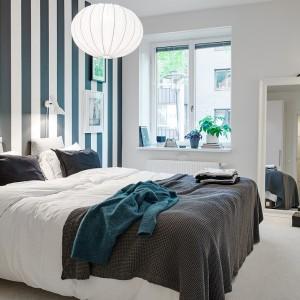 Ściana w czarno-białe pasy wprowadza do sypialni ciekawą dekorację, która narzuca czytelną kolorystykę. Umieszczona tylko na jednej ścianie staje się ozdobą, która nie przytłacza wnętrza.  Fot. Alvhem Mäkler.