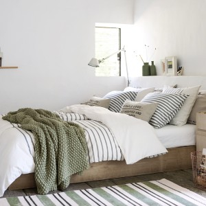 Białe ściany oraz minimalistyczny wystrój tworzy przestronne wnętrze. Fot. H&M Home.