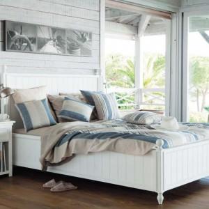 Dobrze oświetlone wnętrze w połączeniu z jasnymi meblami oraz jasną, dekoracyjną ścianą tworzy przytulną sypialnię. Fot. Maison du Monde.