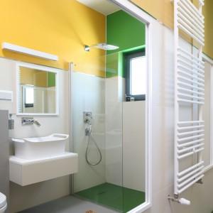 Ogromne lustro w prostej, białej ramie optycznie powiększa przestrzeń łazienki. Jego mniejsza wersja wisi dokładnie naprzeciwko – na ścianie nad umywalką. Fot. Bartosz Jarosz.